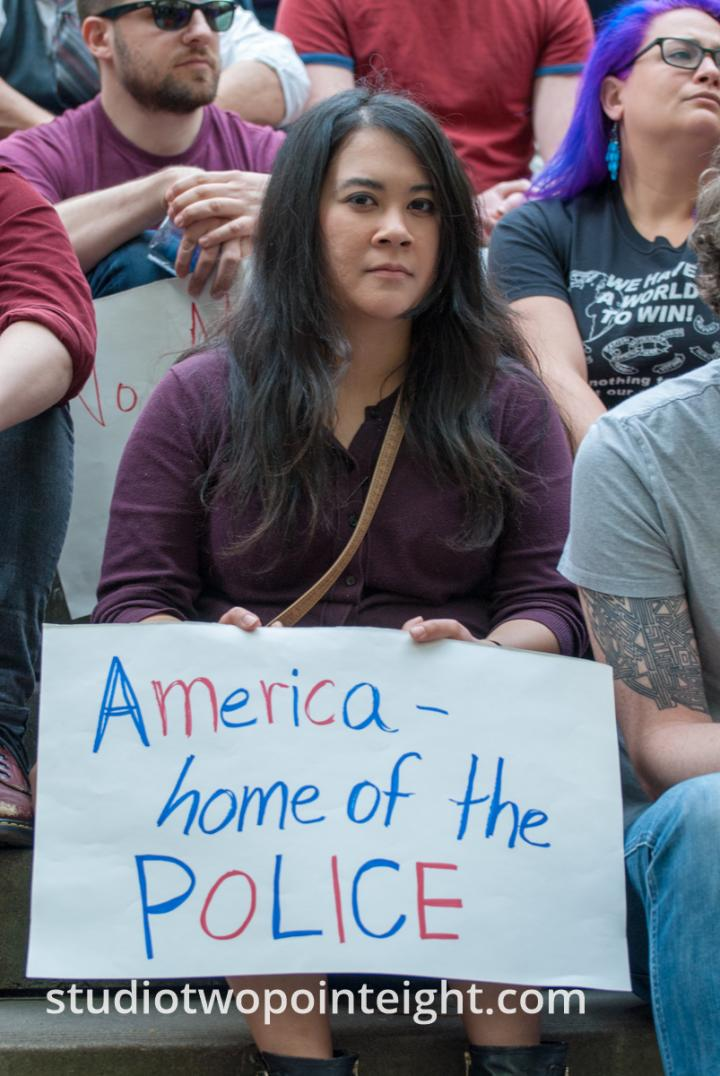 2015 Seattle May Day Immigrant Rally, Woman With American Home Of The Police Poster