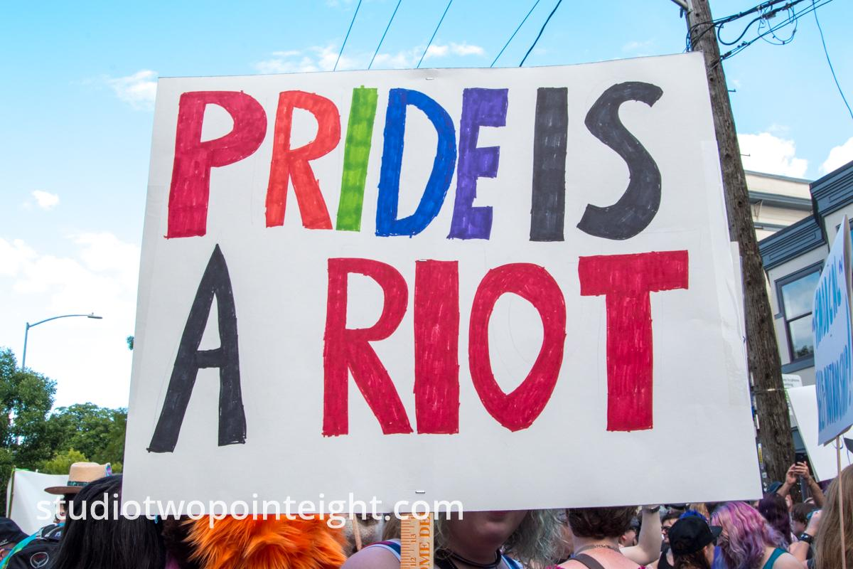 Seattle Trans Pride 2019, An Attendee Held Aloft a Pride Is A Riot Sign