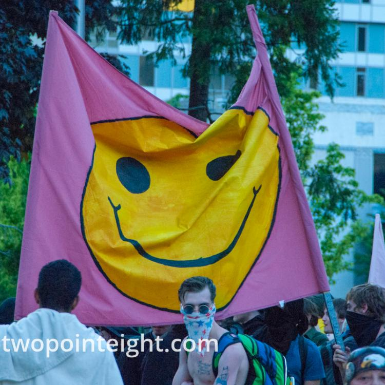 2014 Seattle May Day Protest, Anarchist Black Bloc Protesters Displayed A Smiley Face Theme Flag