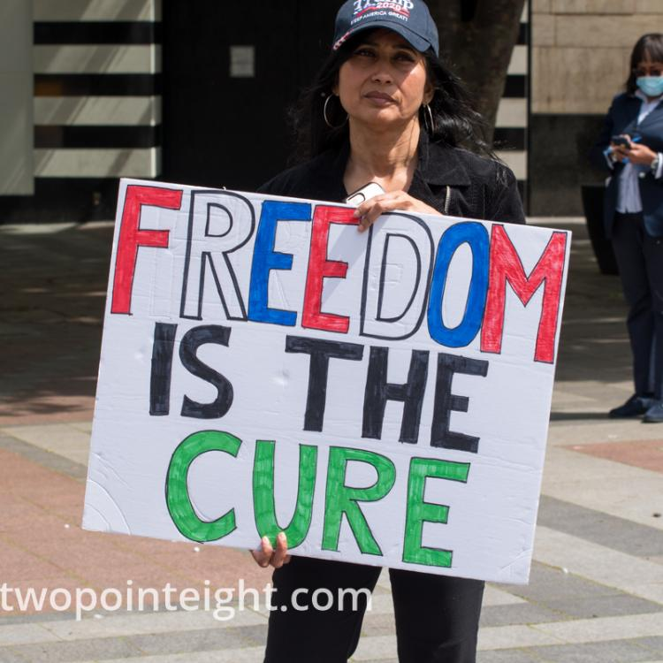 Studio 2.8, May 1, 2020, Seattle May Day End Coronavirus Lockdown Protest, An Attendee Displayed A Large Poster With The Phrase Freedom Is The Cure On It