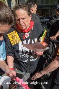 Seattle May 1, 2019 May Day Immigration Rally Woman Passing Out Communist Party Stickers